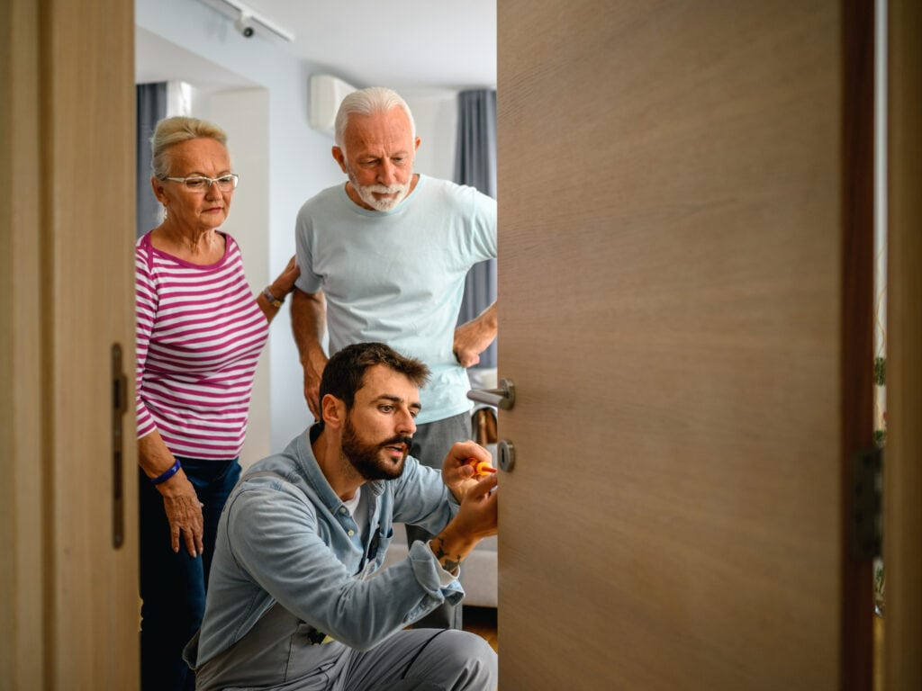 Man fixing a lock on the door while a senior couple is standing next to him.