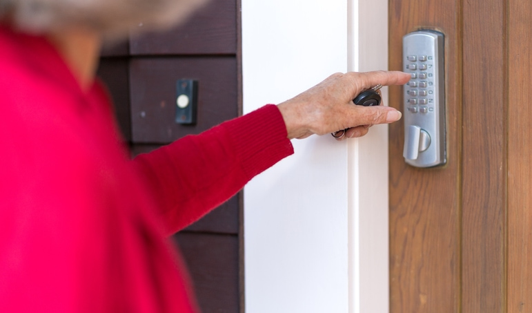 Senior woman uses keyless entry on digital lock to unlock and open domestic front door